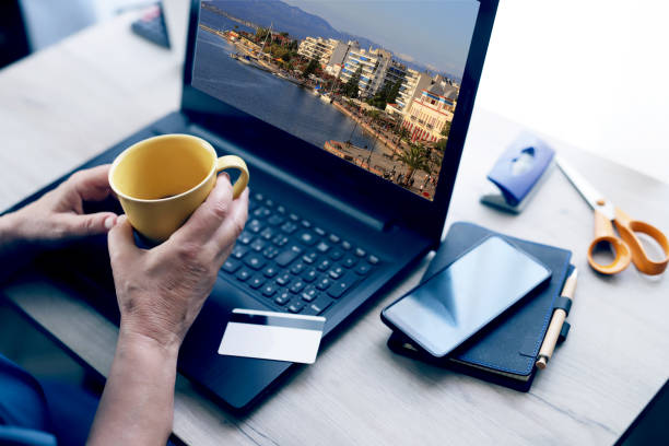 Hands of mature woman with coffee cup in home office stock photo