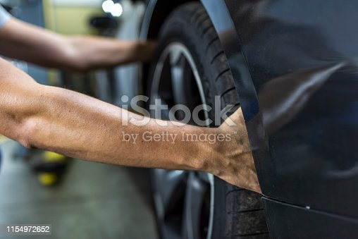 498888104 istock photo Hands of mechanic changing a wheel of a modern car 1154972652