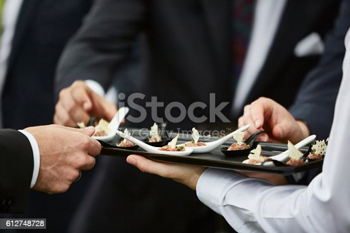 istock Hands of men taking gourmet appetizers served by professional waiter 612748728