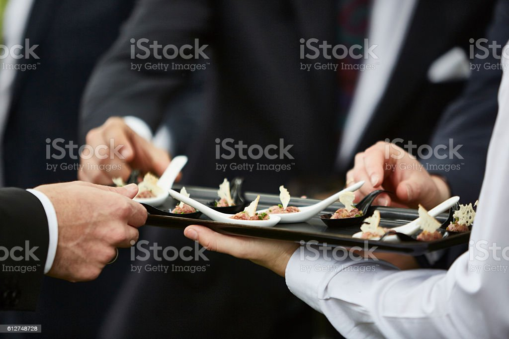 Hands of men taking gourmet appetizers served by professional waiter ストックフォト