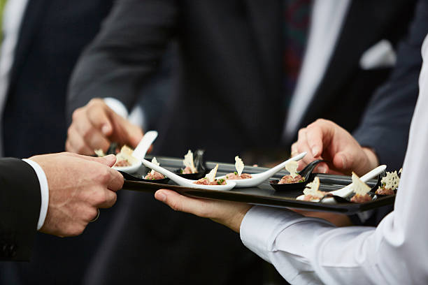 Hands of men taking gourmet appetizers served by professional waiter stock photo