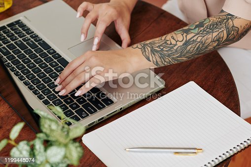 High angle shot of modern young womans hands typing something on laptop