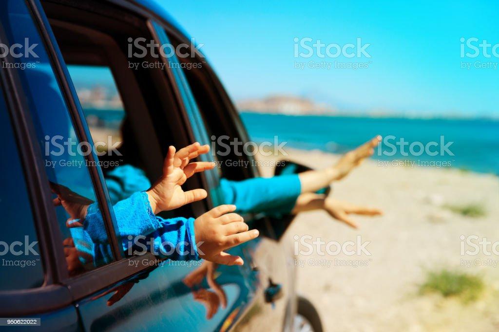 母と子の手はビーチに車で旅行します。 ストックフォト