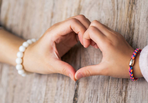 Hands of mother and daughter making heart shape stock photo