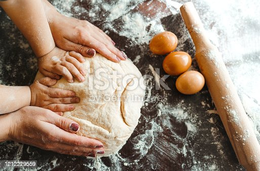 istock Hands of mother and son kneading a dough together. 1212229559