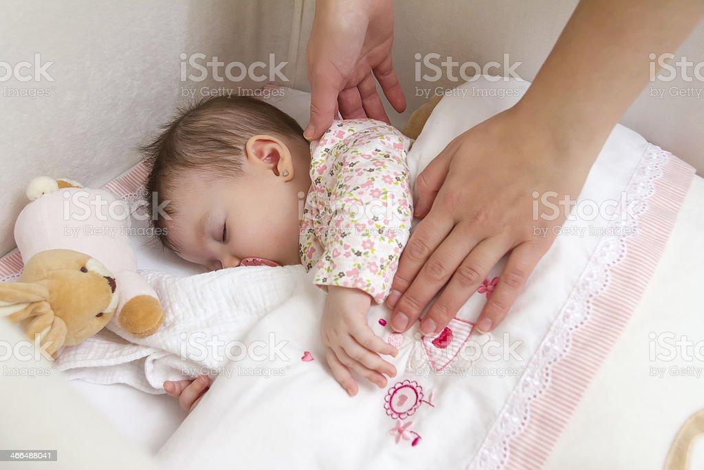 Las manos de la madre caressing her baby girl dormitorio foto de stock libre de derechos