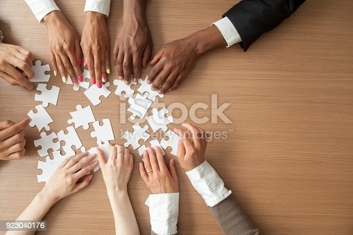 istock Hands of multi-ethnic business team assembling jigsaw puzzle, top view 923040176