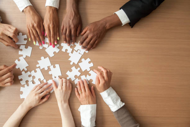 Hands of multi-ethnic business team assembling jigsaw puzzle, top view Hands of multi-ethnic team assembling jigsaw puzzle, multiracial group of black and white people joining pieces at desk, successful teamwork concept, help and support in business, close up top view group corporate stock pictures, royalty-free photos & images
