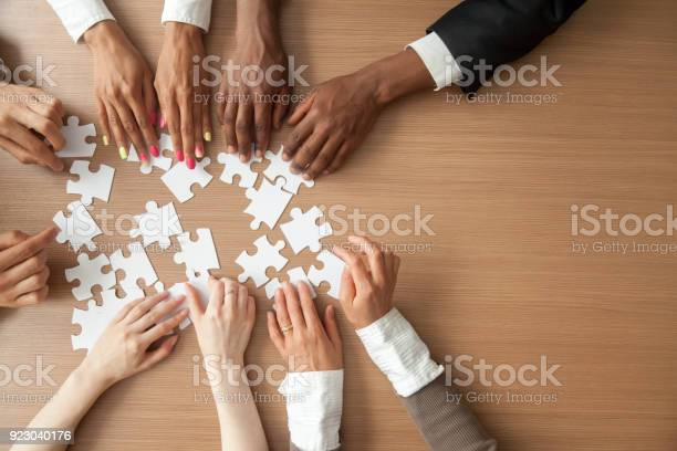 Hands Of Multiethnic Business Team Assembling Jigsaw Puzzle Top View Stock Photo - Download Image Now