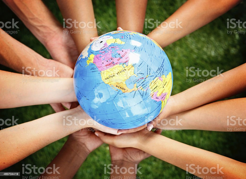 Hands of multi-ethnic group holding Earth stock photo