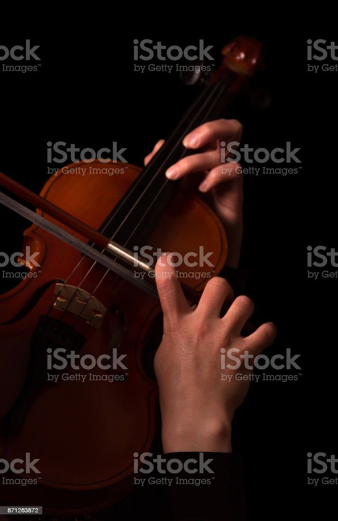 Hands of musician playing the violin isolated on black stock photo