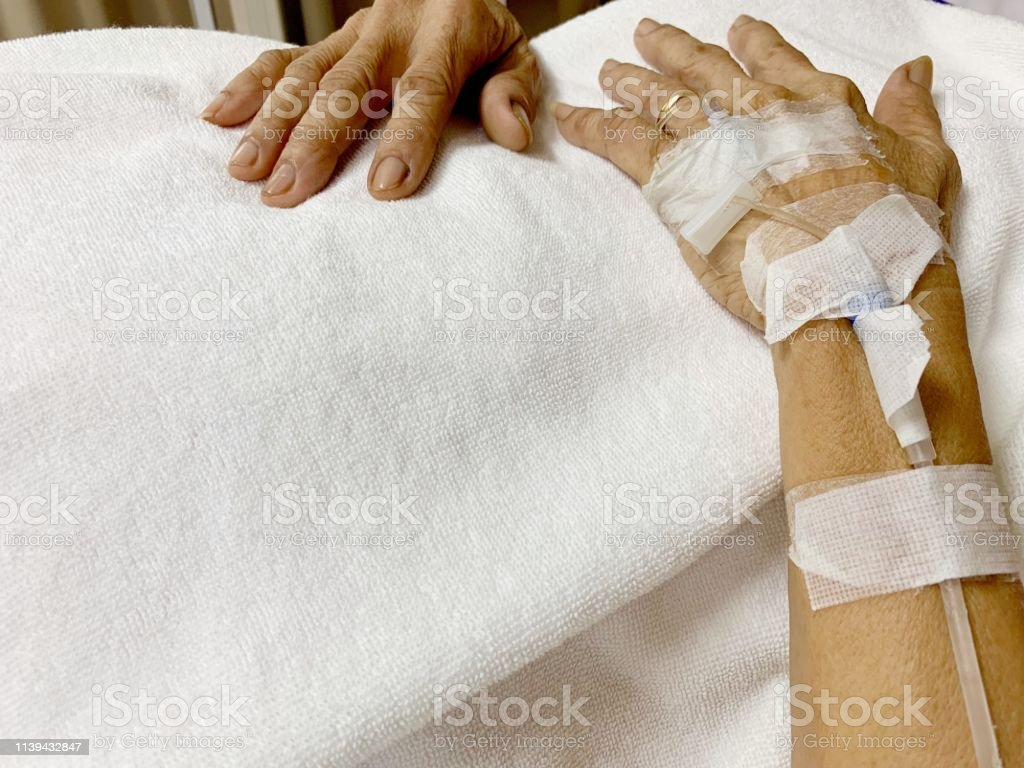 Hands of old age patients with saline solution on a white blanket