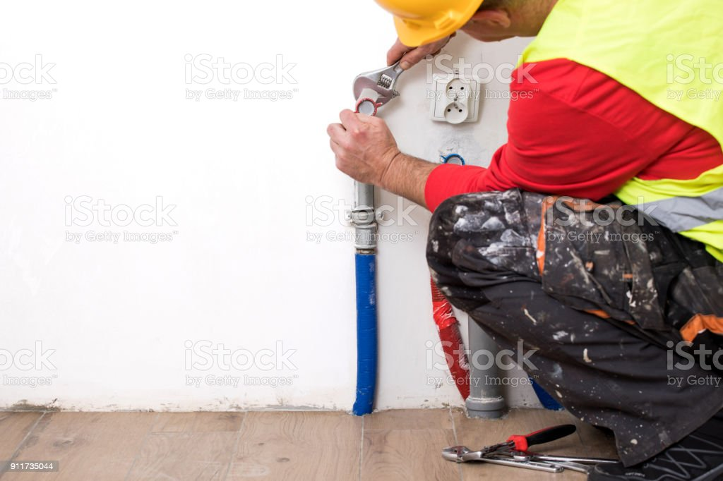 Hands of Plumber with a wrench – zdjęcie
