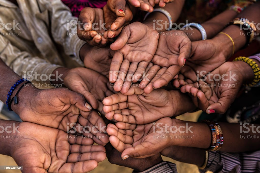 Poor African children keeping their hands up - asking for help. Many...