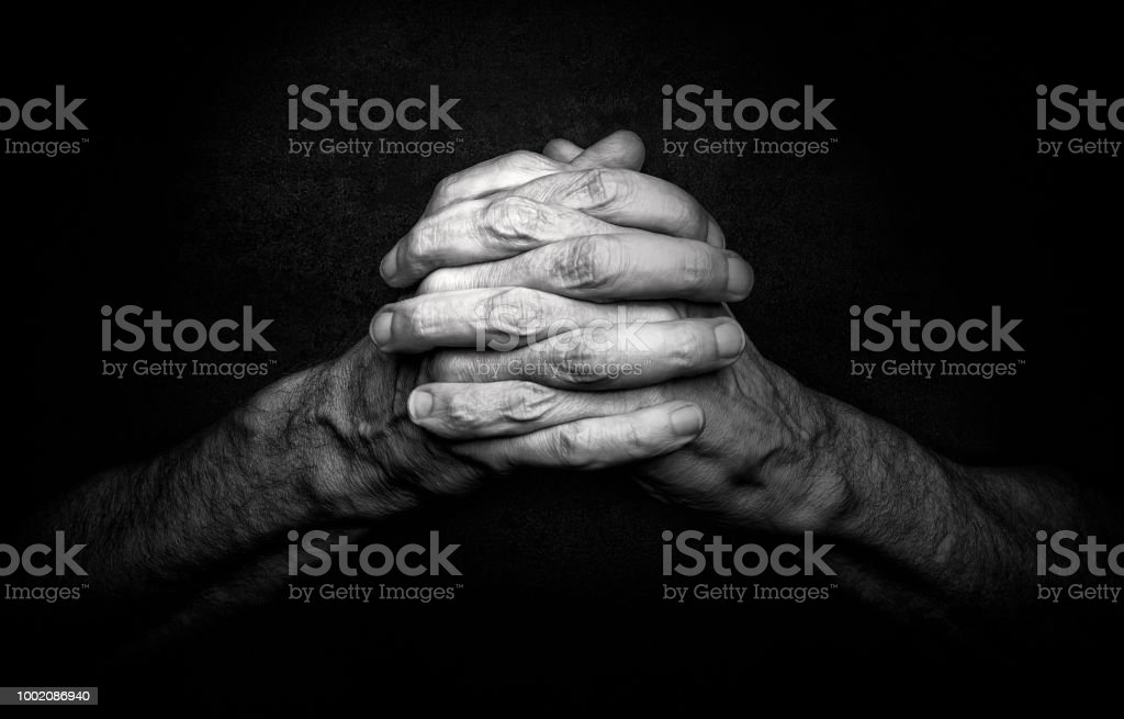 Hands of Praying Man Man's Hands with crossed fingers. This is a classical gesture of a person praying God in the christian religions. Adult Stock Photo