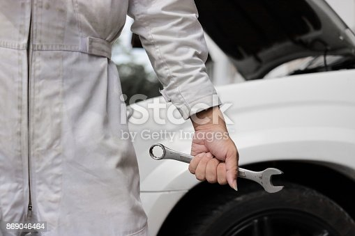 898487280 istock photo Hands of professional mechanic man in white uniform holding wrench with car in open hood at the repair garage background. 869046464