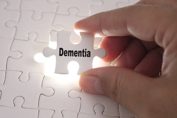 Hands of Professor Doctor holding a jigsaw puzzle with Dementia word. Medical concept. stock photo