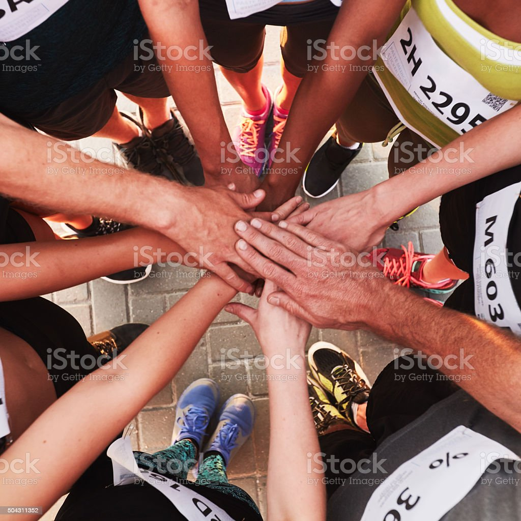 Hands of running team stacked on top of each other stock photo