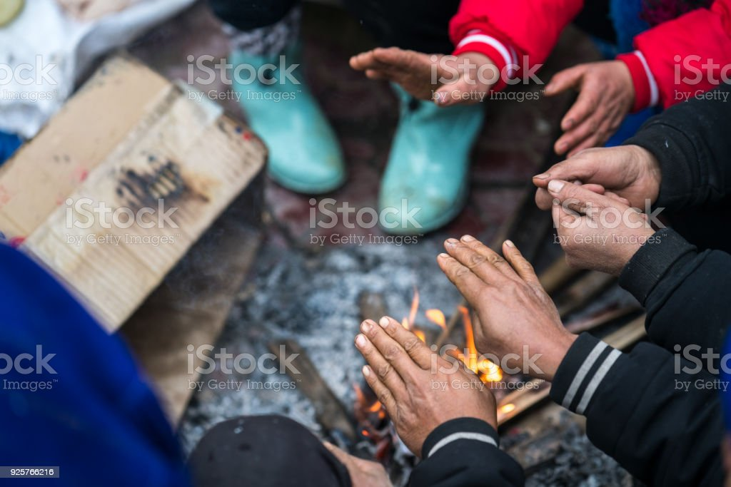 Hands of rural minority people warming up around the fire during the cold weather days in mountaious region in Vietnam stock photo