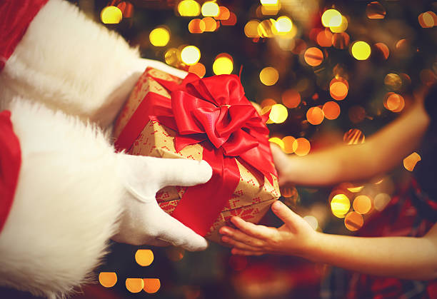 hands of Santa Claus give a child a Christmas gift stock photo