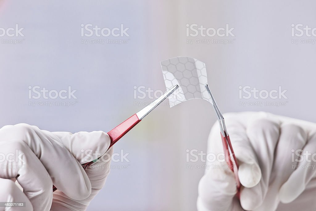 Hands of scientific showing a graphene piece with hexagonal molecule. stock photo