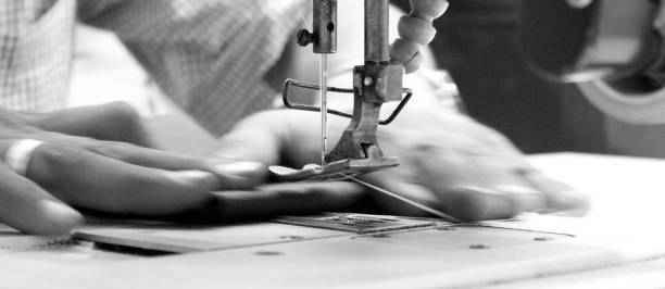 hands of seamstress using sewing machine - sewing machine needle stock photos and pictures
