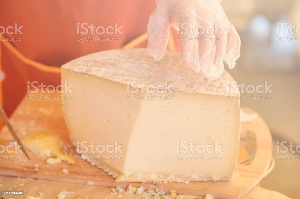 Hands of seller in gloves and half of a large head of cheese close-up, wooden board. Selective focus. Gastronomic dairy produce, real scene, food market stock photo