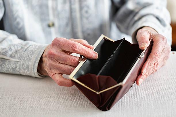 hands of senior adult holding empty purse stock photo