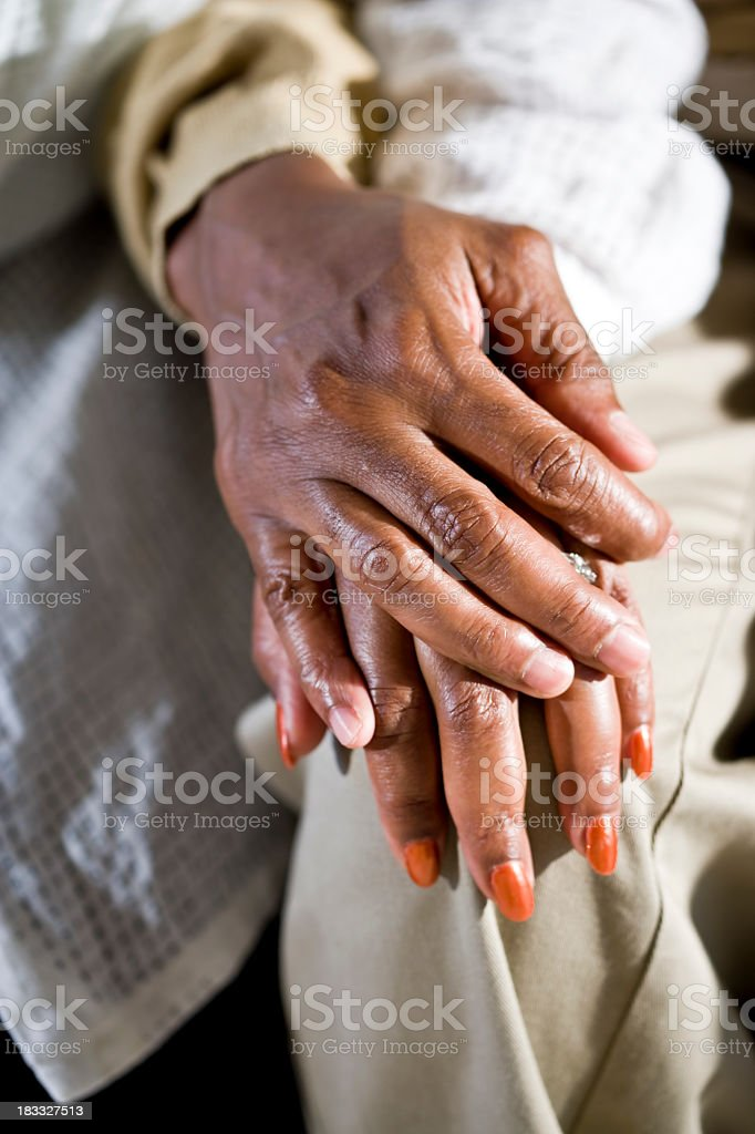 Hands of senior African American couple touching on knee stock photo