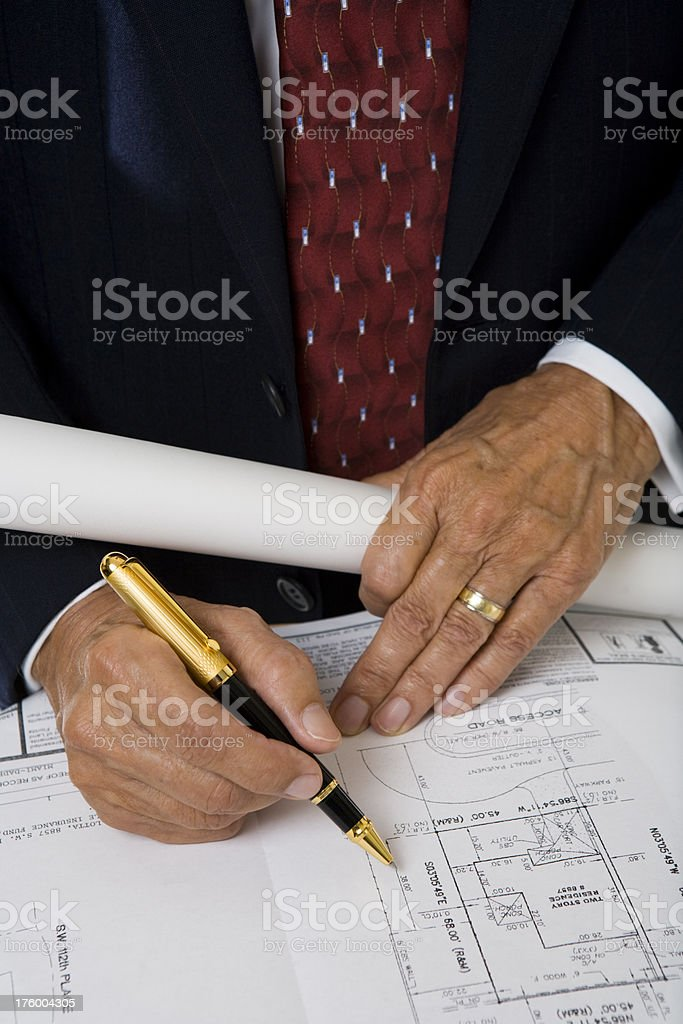 Hands of senior man holding pen on architectural plans blueprints royalty-free stock photo