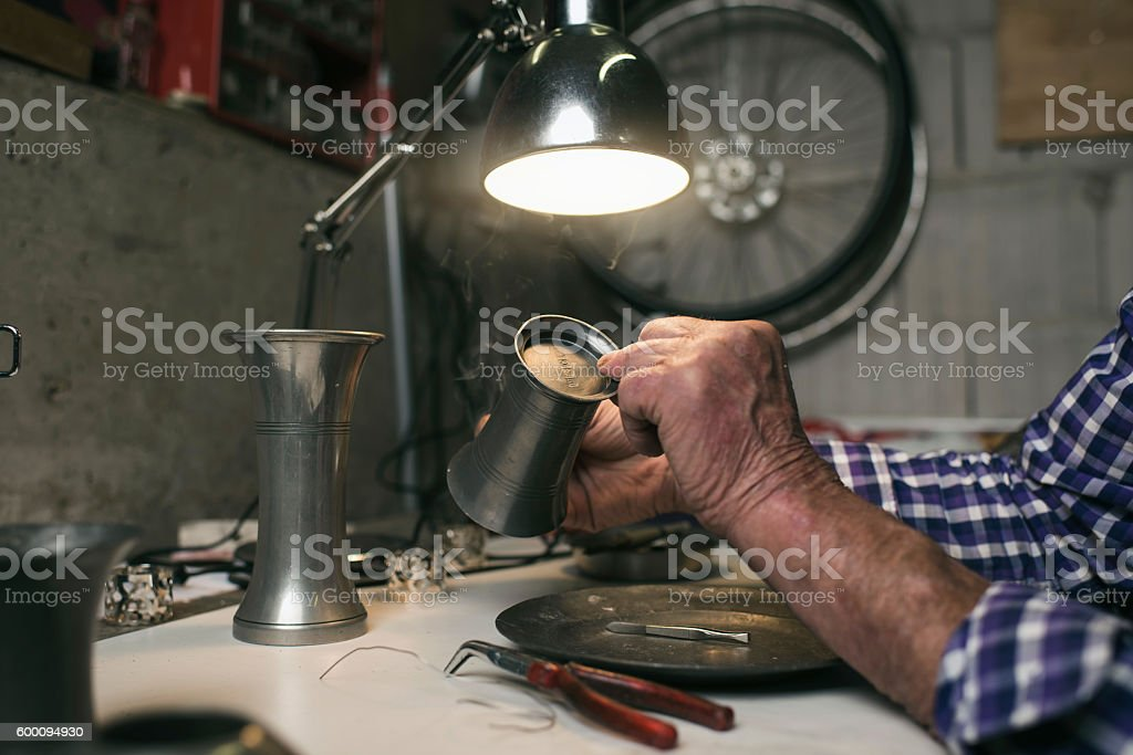 Hands of senior man inspecting antique tin vase stock photo