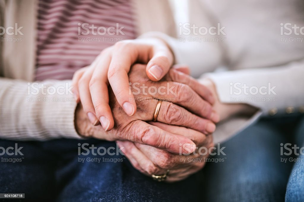 Hands of teenage girl and her grandmother at home. stock photo