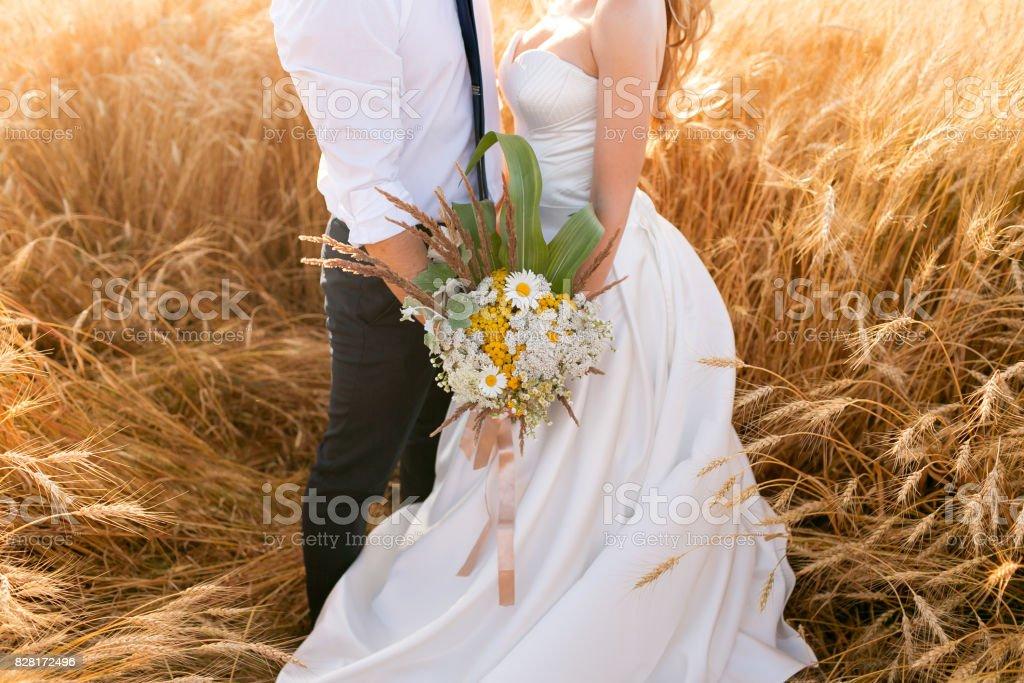 Mains de la mariée et le marié sur le champ de blé. Conte de fées romantique couple de jeunes mariés étreindre au coucher du soleil - Photo