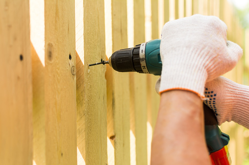 Hands of the carpenter holding electric screwdriver in work close up