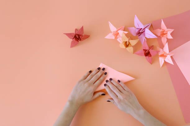 hände der origami-mädchen bringt blumen aus papier von korallen trendfarbe. lektion des origami - origami anleitungen stock-fotos und bilder