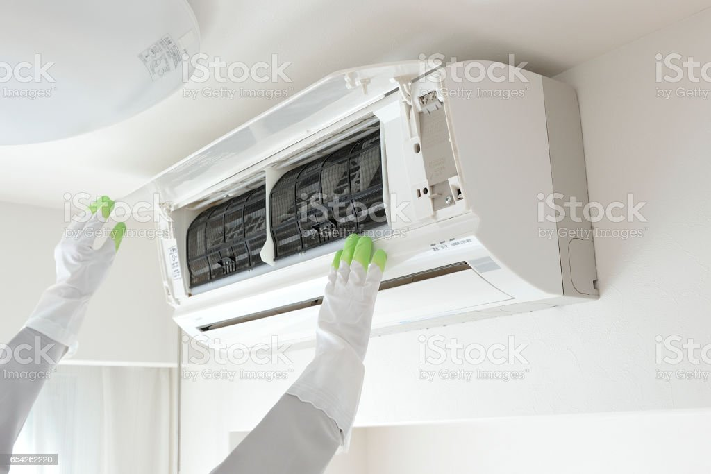 Hands of the people to clean the air conditioner stock photo