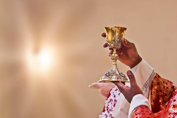 hands of the priest raise the blood of Christ stock photo