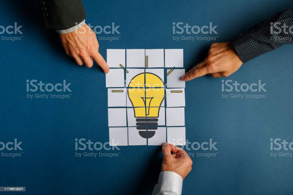 Hands of three businessmen assembling a lightbulb drawn on post it papers Top view of hands of three businessmen assembling a lightbulb drawn on post it papers. Over navy blue background. Achievement Stock Photo