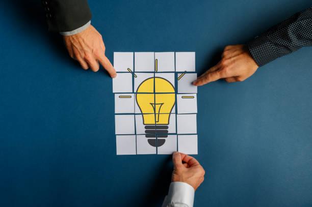 Hände von drei Geschäftsleuten Montage einer Glühbirne auf Post es Papiere gezogen – Foto