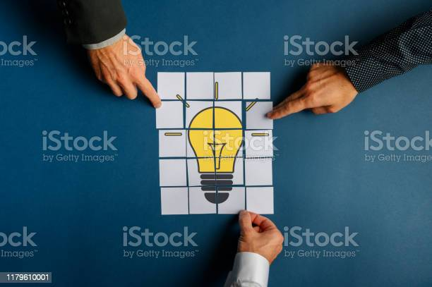 Hands Of Three Businessmen Assembling A Lightbulb Drawn On Post It Papers Stock Photo - Download Image Now