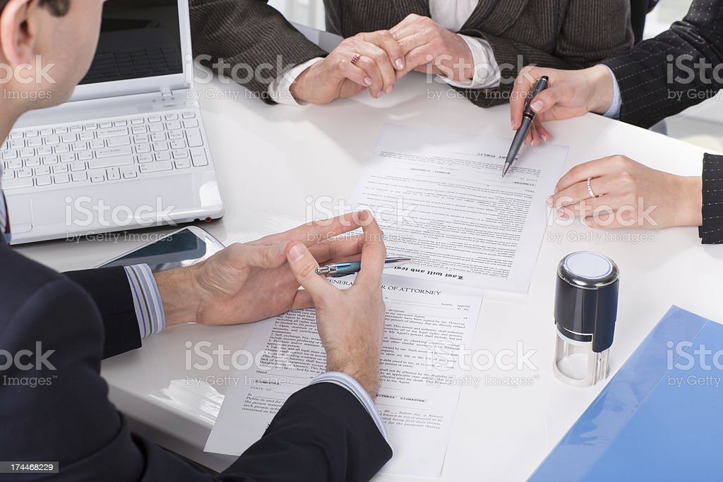 hands of three people, signing documents stock photo