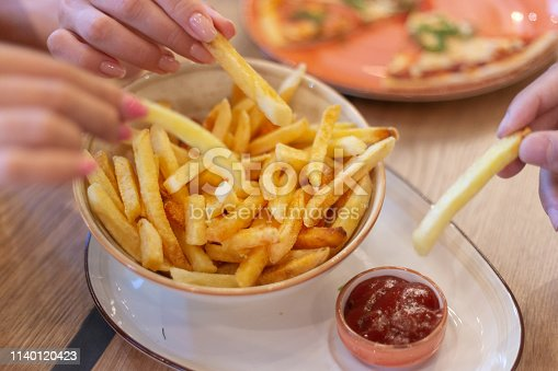 Hands of three young people sharing bowl of french fries and dipping them into ketсhup before eating in restaurant