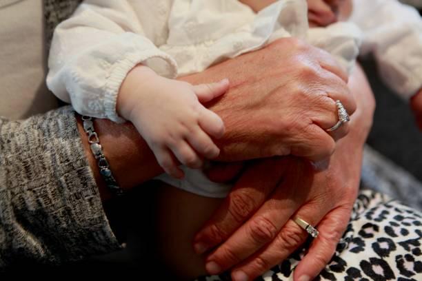 hände der zeit, oma hält enkelin - canda armband stock-fotos und bilder