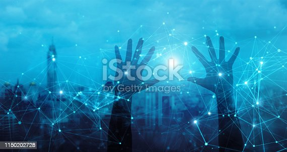 istock Hands of touching global network connection and data exchanges, internet communication on blue city background. 1150202728