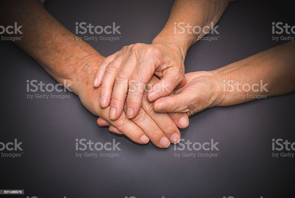 Hands of two loving senior people on a dark background foto stock royalty-free