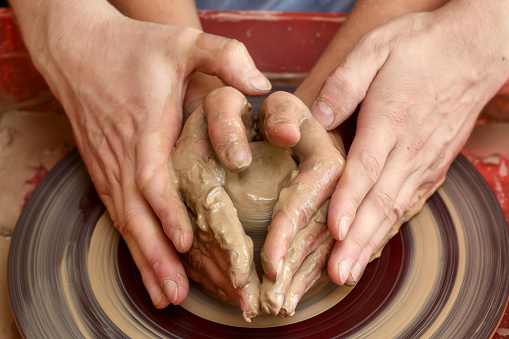 Hands of two people create pot, potter's wheel. Teaching pottery