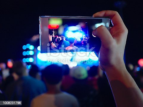 833314292 istock photo Hands of unidentified taking a photo with mobile smart phone of concert stage. 1008231796