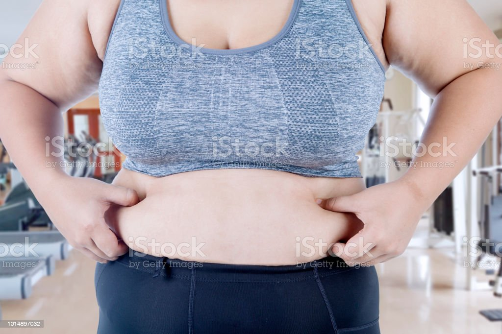Hands of an unknown woman pinching her belly fat while standing in...