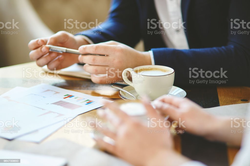 Hands of unrecognizable business people, man and woman, discussing financial strategy over coffee royalty-free stock photo