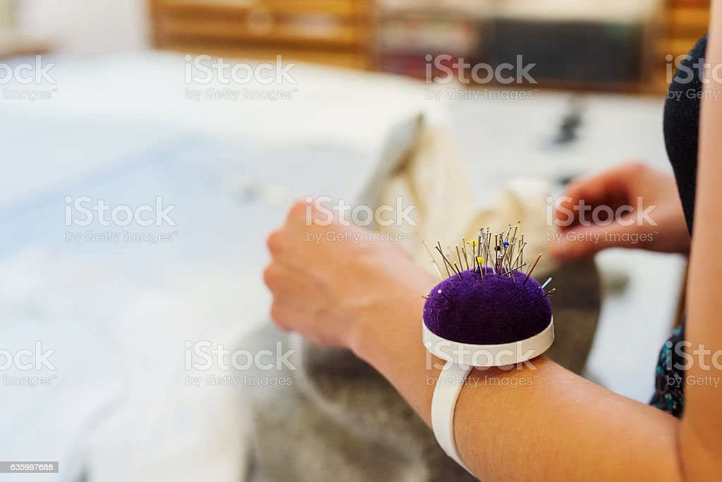 Hands of unrecognizable tailor woman with pin cushion working - foto de acervo
